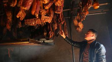 男子在百年老房子里烘腊肉 传承老味道