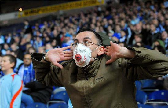 2009 年英国联赛杯的一场比赛中,彼得伯勒联队的球迷在看台上戴着画有猪流感图案的口罩