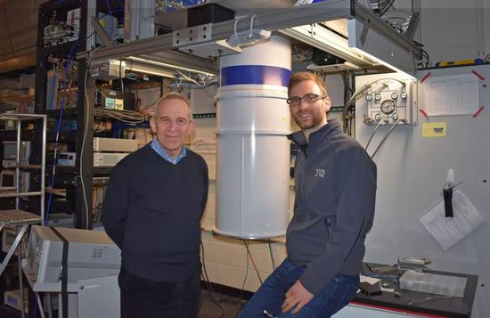 麦克·德沃雷特(左)和兹拉特科·米涅夫站在实验用低温恒温器之前。图片来源:耶鲁大学量子研究所(Yale Quantum Institute)