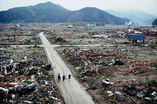 因為幾乎沒有任何預警,致命的日本東北大地震和海嘯摧毀了日本的陸前高田市。災難過后,居民走在廢墟中。
