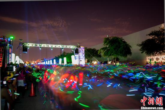 """资料图:美国休斯敦举办""""荧光长跑"""",夜晚现""""霓虹海洋""""。"""