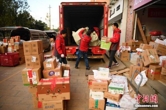 工作人员将分拣后的商品装车。中新社记者 刘冉阳 摄