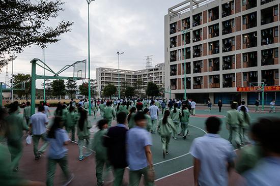 2015年12月24日,放工后,大量员工走过金立工业园体育场。 图片来源:视觉中国