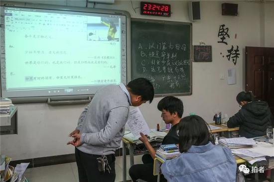 △ 培优班的耿添寿拿着试卷向地理先生挑问。