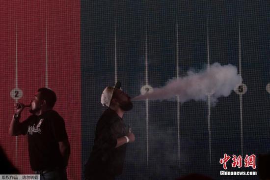"""资料图:墨西哥举办电子烟交易大会,参与者们在大会上用电子烟进行""""吞云吐雾""""。"""