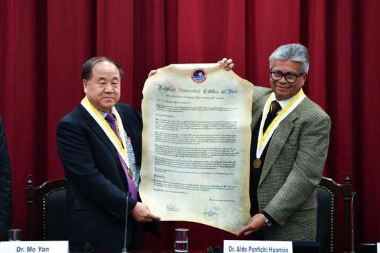 7月30日,在秘鲁首都利马,秘鲁天主教大学副校长阿尔多·潘菲齐·瓦曼(右)向莫言颁发荣誉博士证书。(新华社记者辛悦卫摄)