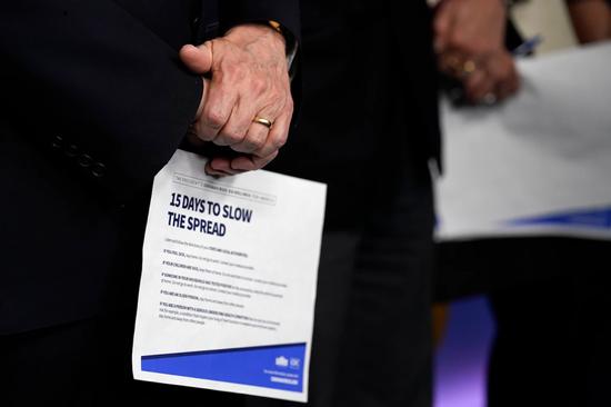 副总统彭斯周一在与冠状病毒特别工作组的新闻发布会上拿着一张信息表。(Evan Vucci / 美联社)