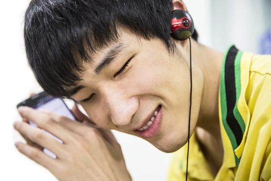 """一名视障者正在""""听""""手机。深圳市信息无障碍研究会供图"""