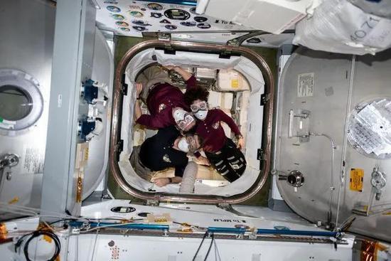 """在国际空间站,""""远征62""""任务的宇航员在SpaceX公司的龙飞船CRS-20补给舱内摆好姿势拍照。他们戴的面罩是为了抵挡龙飞船在飞行时可能产生的颗粒或刺激物"""