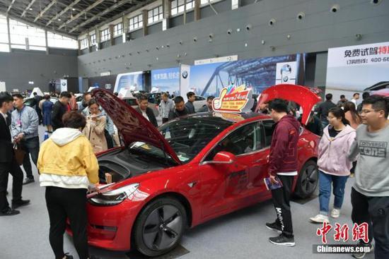 2019年4月19日,美国特斯拉电动车展区人来人往,参观者驻足观赏、试乘体验。中新社记者 翟羽佳 摄