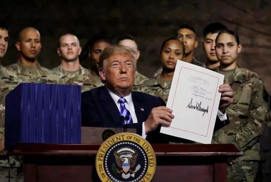 """资料图片:2018年8月13日,特朗普签署""""2019年度国防授权法""""。(路透社)"""