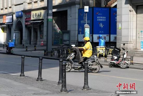 图为街上的外卖小哥。中新社记者 安源 摄