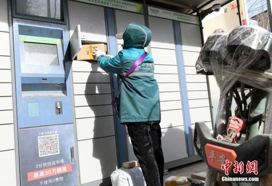 资料图:石家庄一快递员将快递物品放入收货柜。 中新社记者 陈昊 摄
