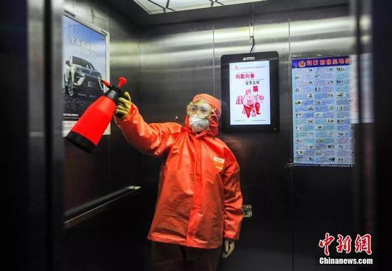 1月29日,新疆乌鲁木齐市南昌路社区工作人员为辖区一公共电梯间进行消毒。中新社记者 刘新 摄
