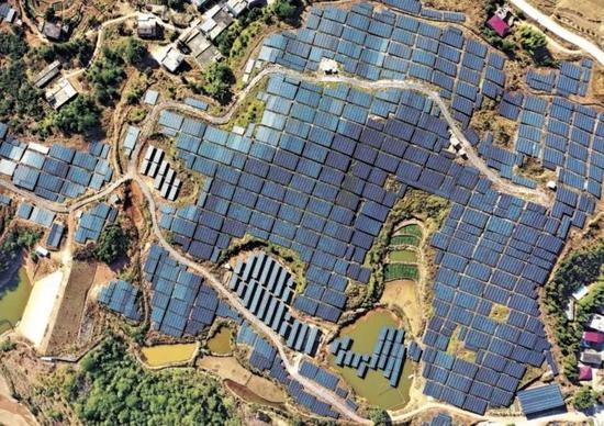 2021年1月4日,江西省赣州市会昌县庄口镇黄沙村的贫瘠荒山上建起光伏扶贫电站,鳞次栉比的蓝色光伏聚能板为国家电网持续提供着绿色能源。(供图 视觉中国)