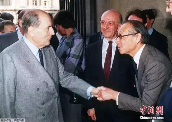 1989年3月29日,法国前总统密特朗(左)在出席巴黎卢浮宫金字塔开幕式时与贝聿铭(右)握。(资料图)