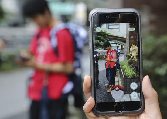 """2016年7月22日,在日本东京,别名弟子用智能手机玩""""精灵宝可梦GO""""(新华社/美联)"""