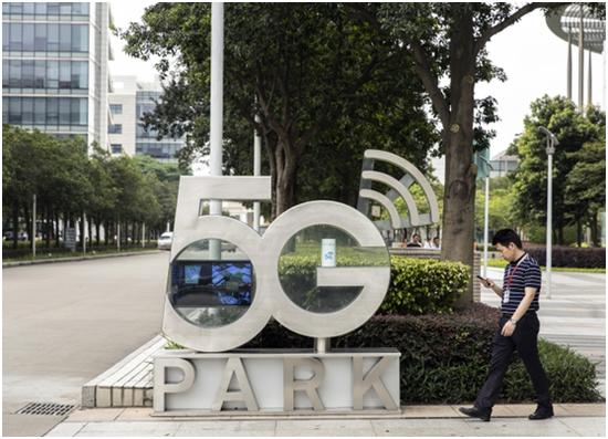 一名员工走过华为5G公园标牌,图源:彭博社