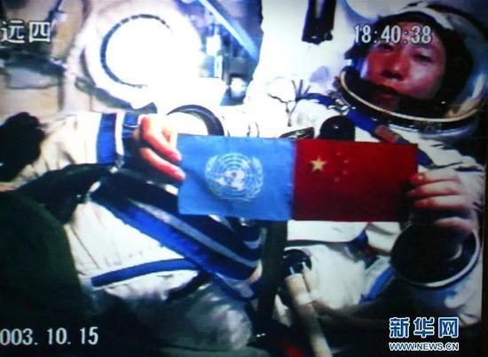 北京时间2003年10月15日18时40分,中国培养的第一位航天员杨利伟从太空向世界各国人民问好,并在舱内并列展示了五星红旗和联合国旗(资料照片,摄于北京航天指挥控制中心大屏幕)。新华社发
