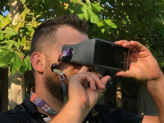 在将手机塞入双目镜后,用户的手指可以从底部空隙处伸入以操控屏幕。