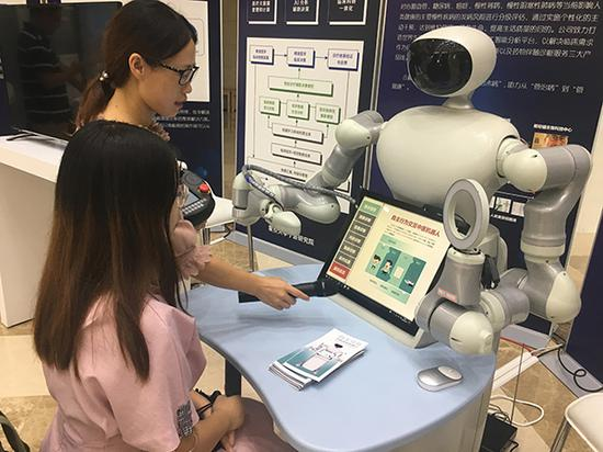 罗静静博士向体验者演示中医体检机器人。 澎湃资讯见习记者 朱奕奕 图