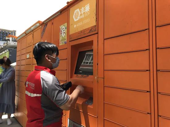 在朝阳区天泰北双苑小区,由于收件人无法及时收货,京东物流快递员将快递放在丰巢柜里。新京报记者 罗晓静 摄