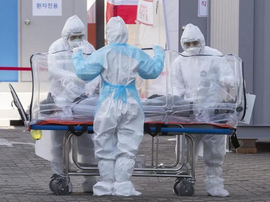 3月11日,在韩国首尔,医护人员将一名患者从救护车转送至医院。新华社发(李相浩 摄)