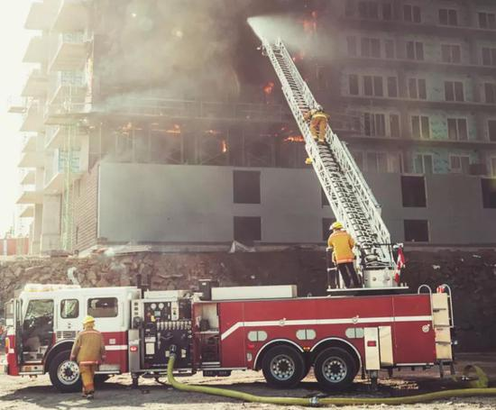 消防员借助消防梯实施灭火救援(图片来源:veer图库)
