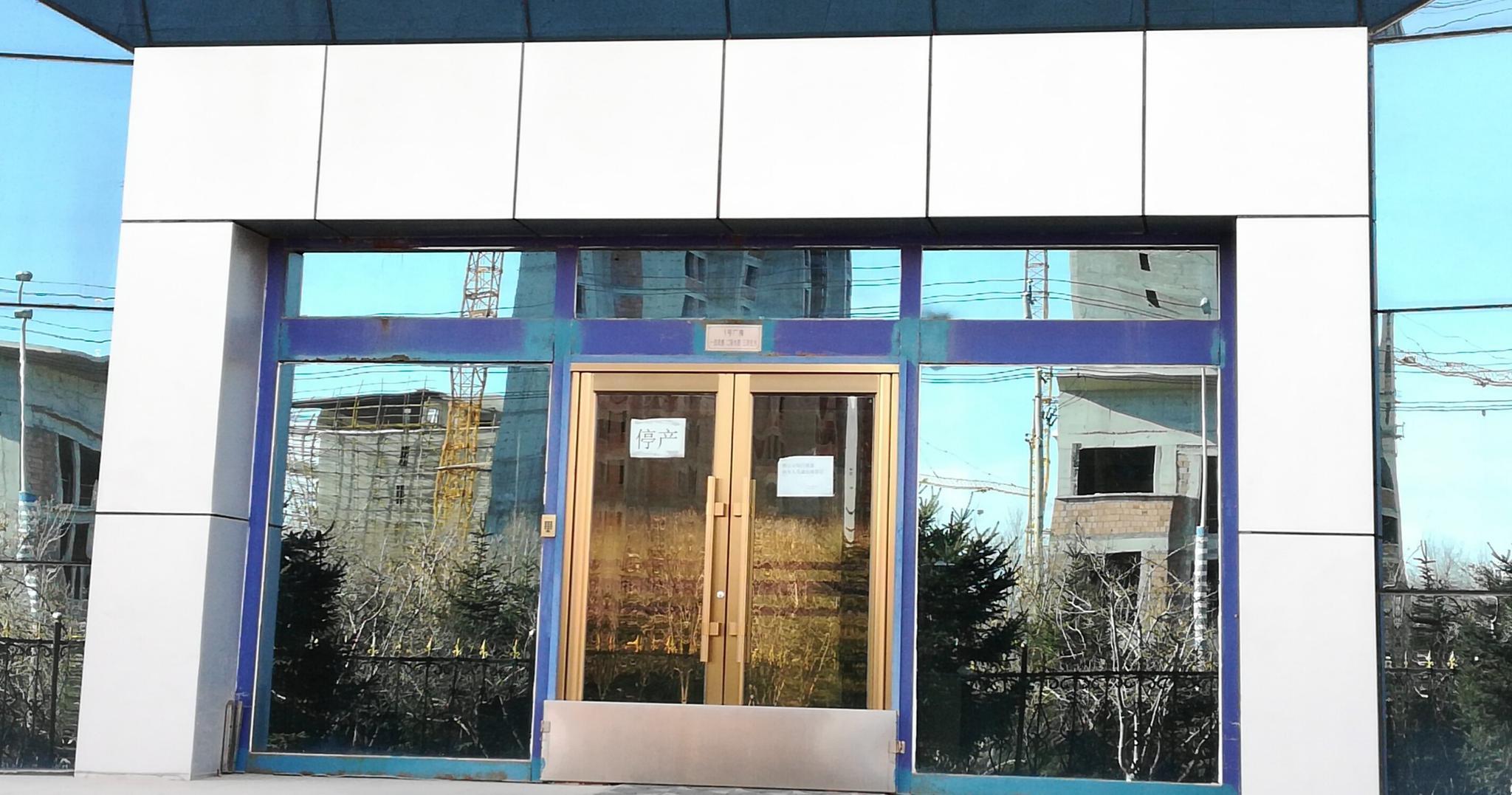 """12月7日,长生生物能够生产水痘、狂犬、流感疫苗的1号厂房一侧入口,门上贴着""""停产""""提示。摄影/新京报记者 李云琦"""