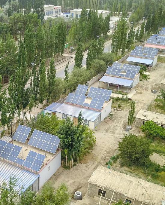 巴音郭楞州南部且末县某乡下的分布式光伏发电设备| 太阳能发电板装配在村民的房顶上,日常发电自用,闲时余电入网,能够为村民创收。图源@VCG