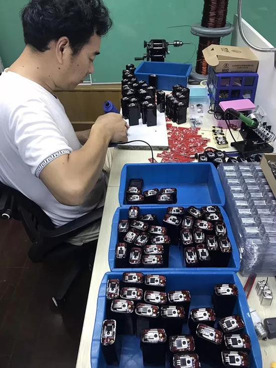 生产车间工人在组装小黑盒。