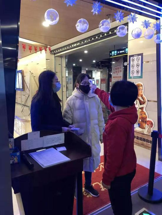 1月23日,通知暂停营业那天,湖北荆州一家华夏国际影城在给员工测量体温(受访者供图)