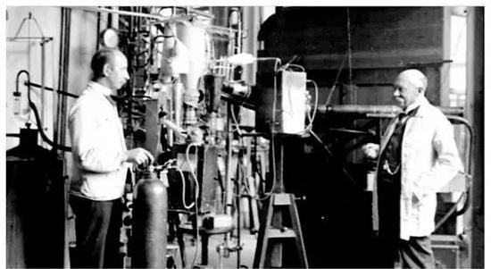 图 | 卡 末 林•昂 内 斯 (右 ) 和 他 的 实 验 员 盖 芮 特�卜� 立 姆 (左 ) 于 1911 年 在 世界上首台氦液化器旁的照片
