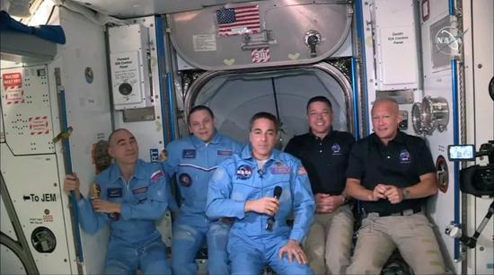 国际空间站上的宇航员与龙飞船上的宇航员相聚场景。| 图片来源:视觉中国