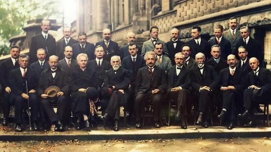 """图5:1927年10月于比利时布鲁塞尔召开的第五次索尔维会议合影。此次会议主题为""""电子与光子"""",是 专门为讨论新近建立的量子力学而举行的。虽然量子力学基本框架得到了广泛的认同,但就量子力学的诠释问题,会上的两位主角爱因斯坦与玻尔产生了激烈的交锋,这拉开了几乎持续了数?年的所谓""""玻尔-爱因斯坦论战""""的序幕。图中几乎所有人都对量子力学或现代物理做出了重大贡献,下面列出他们每一个人的名字,以示崇高的敬意与铭记。每排皆按从左至右排。第3排:奥古斯特·皮卡尔德,亨里奥特,保罗·埃伦费斯特,爱德华·赫尔岑,西奥费·顿德尔,埃尔温·薛定谔,维夏菲尔特,沃尔夫冈·泡利,维尔纳·海森堡,拉尔夫·福勒,莱昂·布里渊;第2排:彼得·德拜,马丁·努森,威廉·劳伦斯·布拉格,亨德里克·克雷默,保罗·狄拉克,阿瑟·康普顿,路易·德布罗意,马克斯·玻恩,尼尔斯·玻尔;第1排:欧文·朗缪尔,马克斯·普朗克,玛丽·居里,亨德里克·洛伦兹,阿尔伯特·爱因斯坦,保罗·朗之万,查尔斯·古耶,查尔斯·威耳逊,欧文·理查森。"""