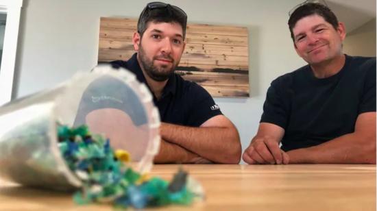 ▲ JD Composites 创始人坐在'塑料房'里。桌面的塑料碎片显示了回收过程的第一阶段。图片来自:Brett Ruskin / CBC