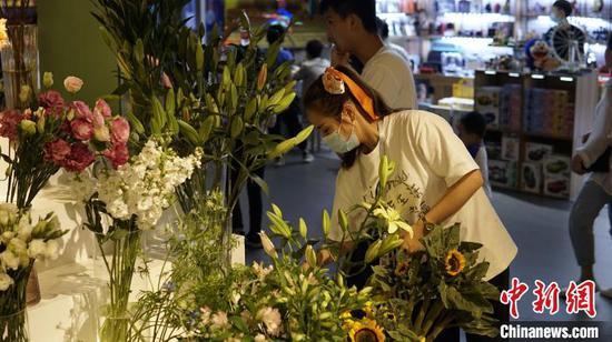 女性市民在花店内为自己购买鲜花。 莫德令 摄