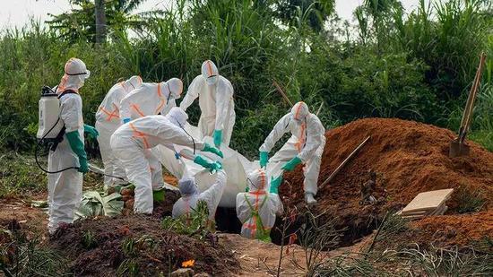 上周,医护人员在处理一名死于埃博拉的患者的遗体。(来源:AP PHOTO/JEROME DELAY)