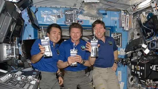 国际空间站宇航员正在快乐的引用由尿液净化得到的纯净水。(图片来源:NASA)