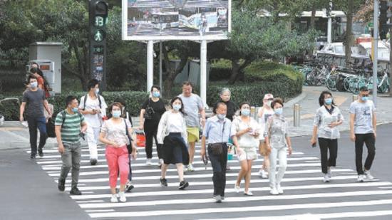 昨天,在中关村西区新中关购物中心门前,行人通过智能斑马线过街。本报记者 饶强摄
