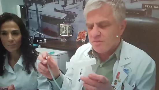"""纳迪尔·阿尔伯在视频会议中展示""""服药""""设备。图片来源:会议视频截图"""