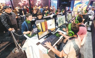 6月12日,在美国洛杉矶,人们在E3电子娱乐展上体验电子游戏。新华社/法新