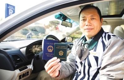 山东泰安,一位网约车司机展现手中的网约车从业资格证。   原料图片