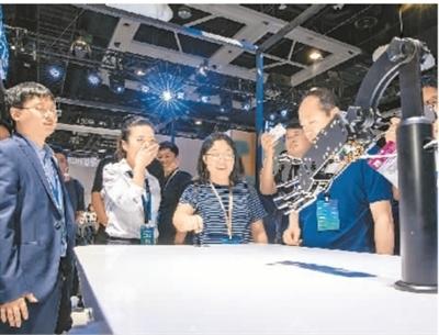 5月31日,在辽宁省沈阳市,第二届信息化展示大会的参会人员在与机械手臂互动。   张大为(人民视觉)