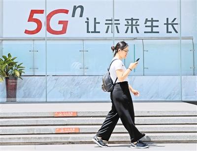 6月3日,在北京西单,一名女子从一块5G广告牌前走过。   新华社记者 才 扬摄