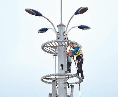 中国铁塔股份有限公司工作人员在长沙市天心区披塘路5G基站上加挂5G天线。 新华社发