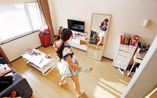 一名愛好Cosplay的房客在魔方公寓房間里練習舞蹈動作。圖/新華