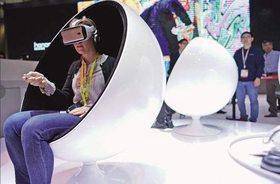 2017年1月5日,在美国拉斯维添斯消耗电子展上,参不都雅者操纵华为手机体验虚拟现实技术。图/新华