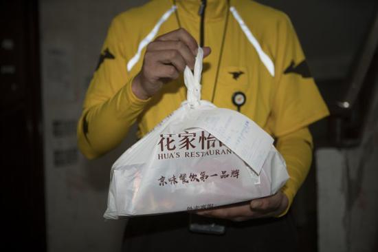 美团点评外卖小哥张俊涛(Zhang Juntao,音)手里拿着准备送达的外卖单。图片:《华尔街日报》Giulia Marchi
