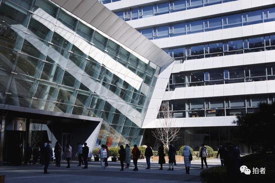 3月13日上午,西二旗中关村软件园,员工排队测温进公司大楼。